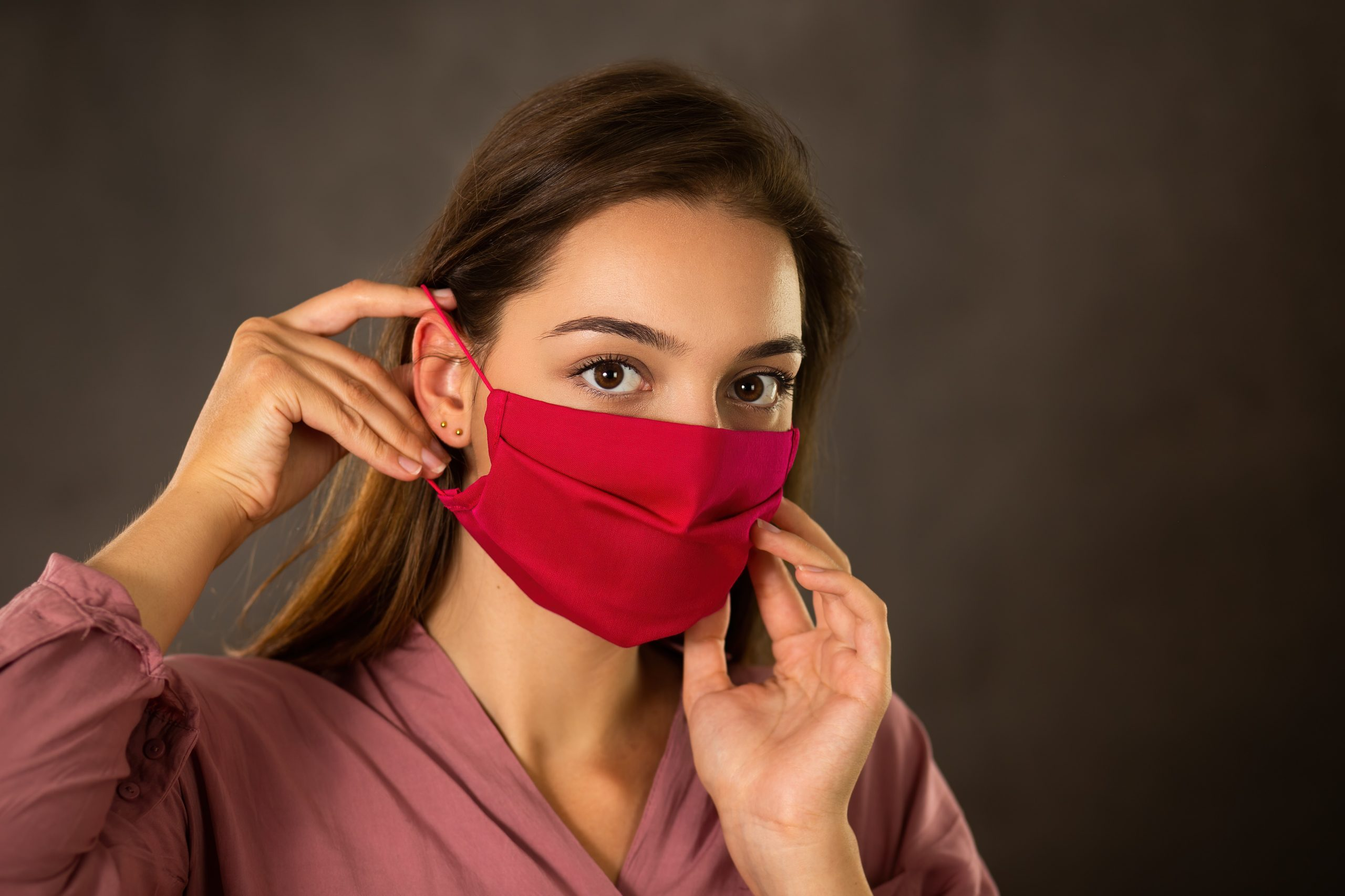 woman-attaching-red-cloth-face-mask-on-ear